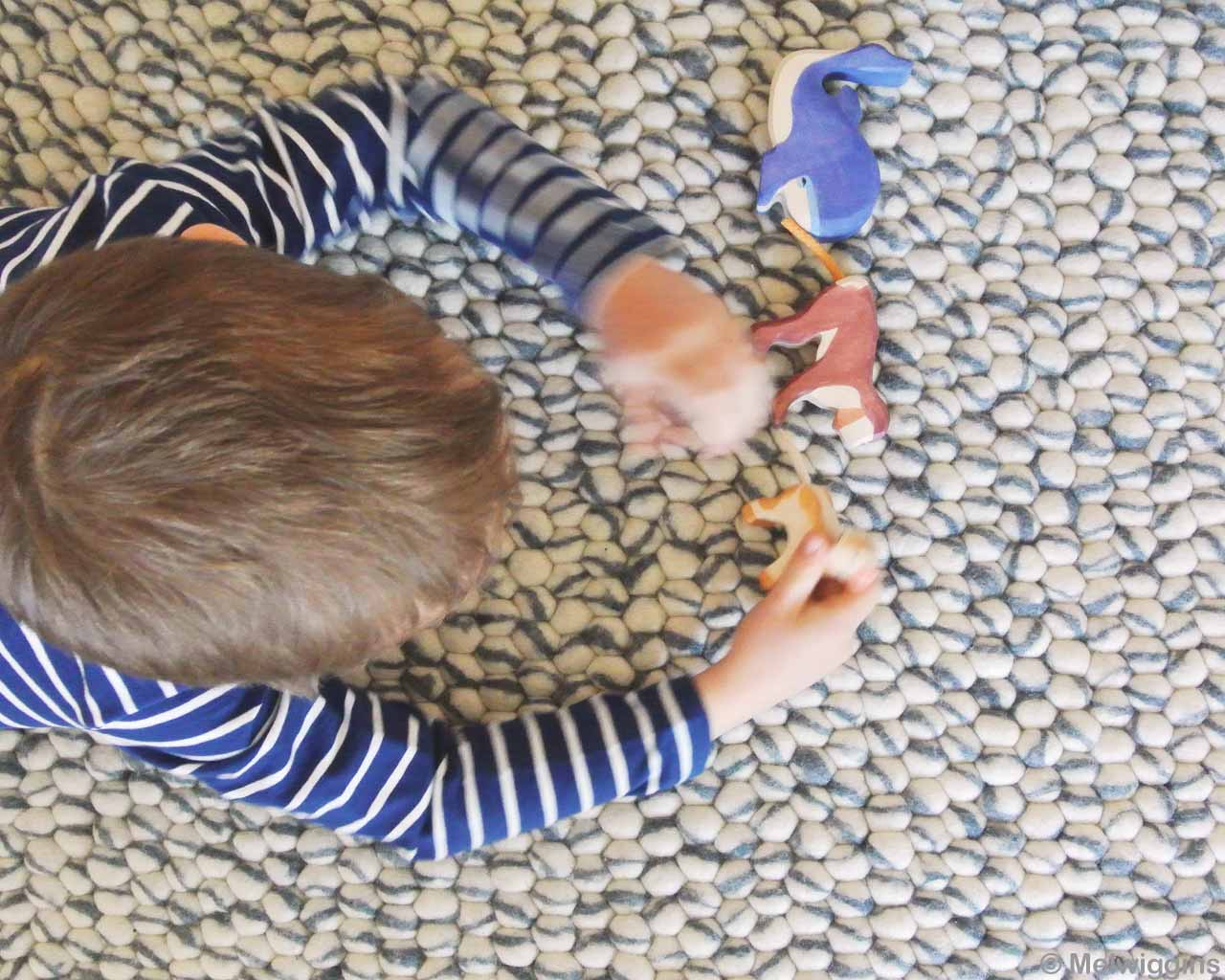 little boy on carpet playing with toys 1